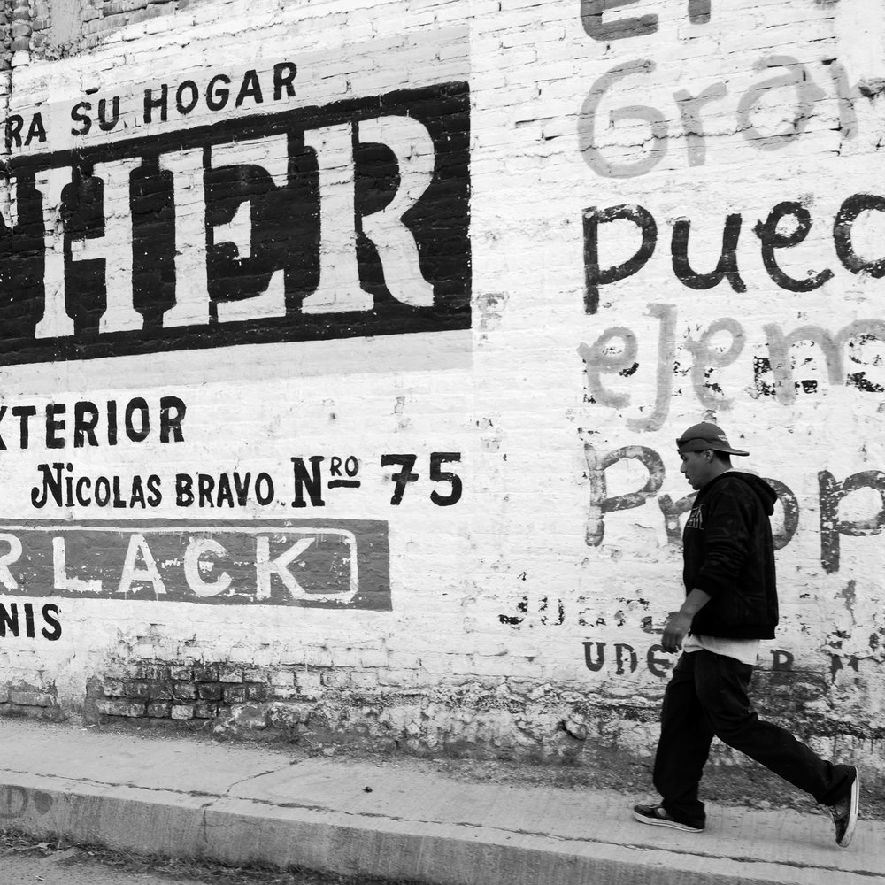 A man walks by a wall painted with advertising and graffetti in a small Mexican town.
