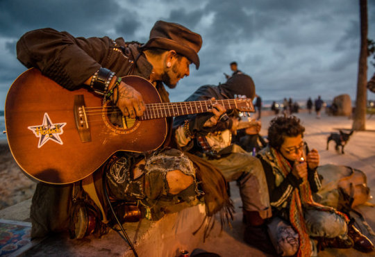 A homeless man plays guitar and sings with other friends at Ocean Beach California.