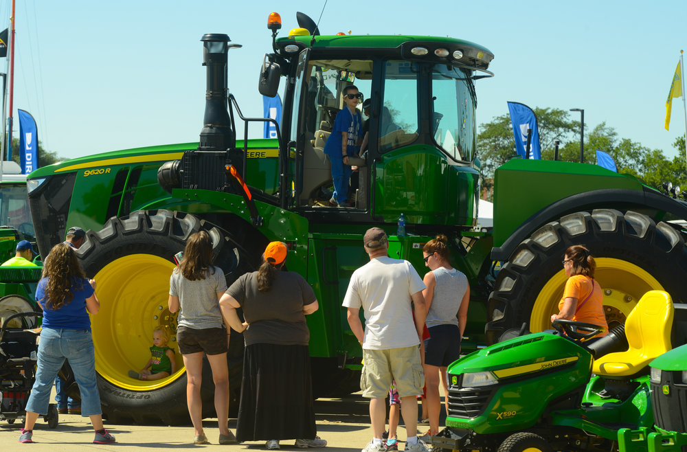 Visitors to the Iowa State Fair in Des Moines, Iowa look at a new John Deere tractor. New equipment sales have been sluggish in the face of a worsening farm economy. (Photo: Joseph L. Murphy)