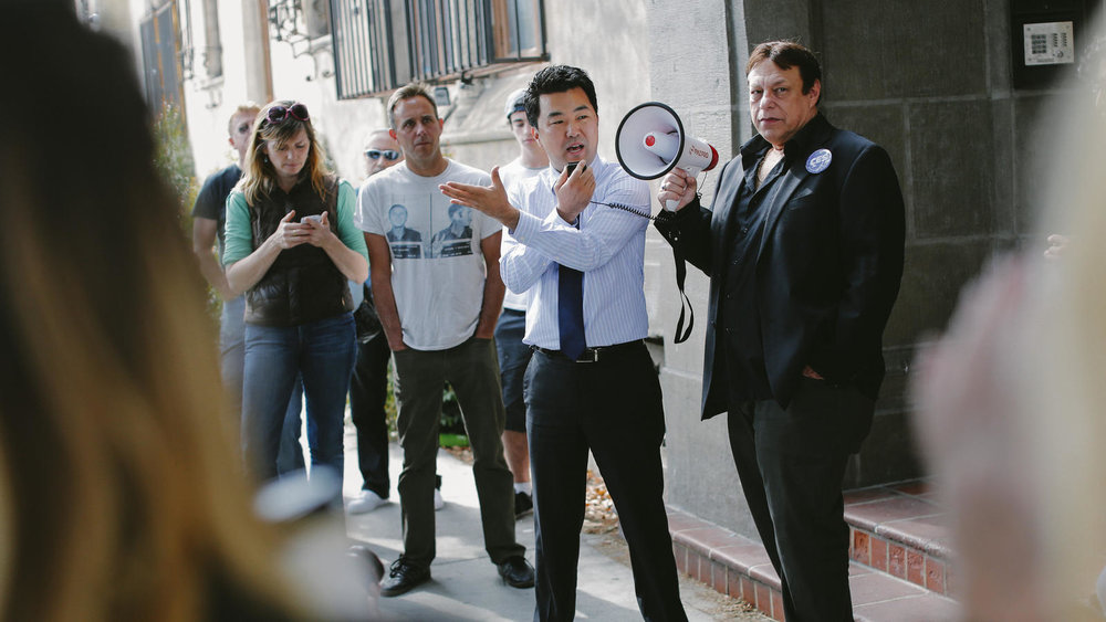Then-L.A. City Council candidate David Ryu speaks in 2015 at a rally organized by Larry Gross, right, with the Coalition For Economic Survival, for residents of the Villa Carlotta apartment building in Hollywood. (Jay L. Clendenin/Los Angeles Times)