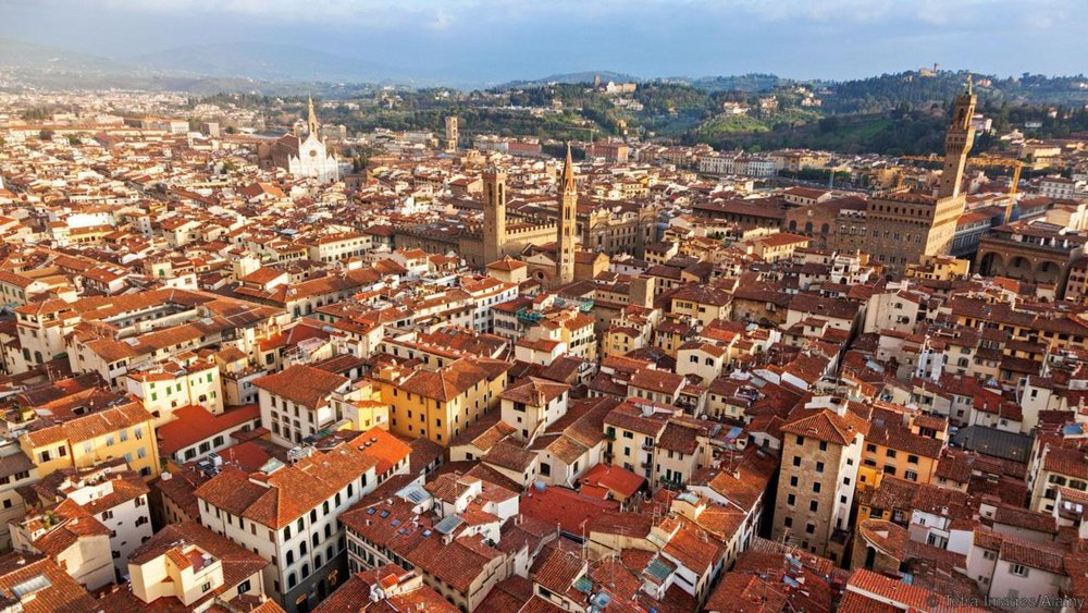 Ariel view of Florence: The white church is Santa Croce. This maze of terra-cotta rooftops is our neighborhood. These are our people.