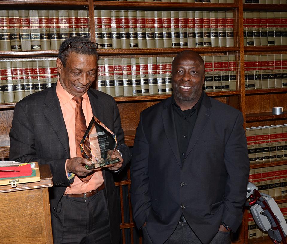 "John Artis admires the award he received on behalf of the late Rubin ""Hurricane"" Carter.David McCallum made the presentation"
