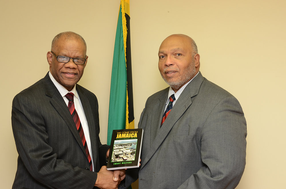Ewart Walters (r) presents a copy of his new book to Jamaica's consul general George Ramocan