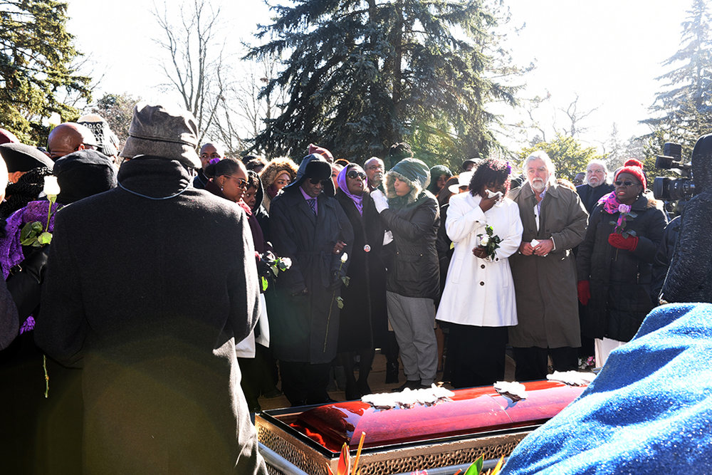 A grieving Olivia Grange in purple scarf and Gifford Walker in purple shirt with black hat at the burial site