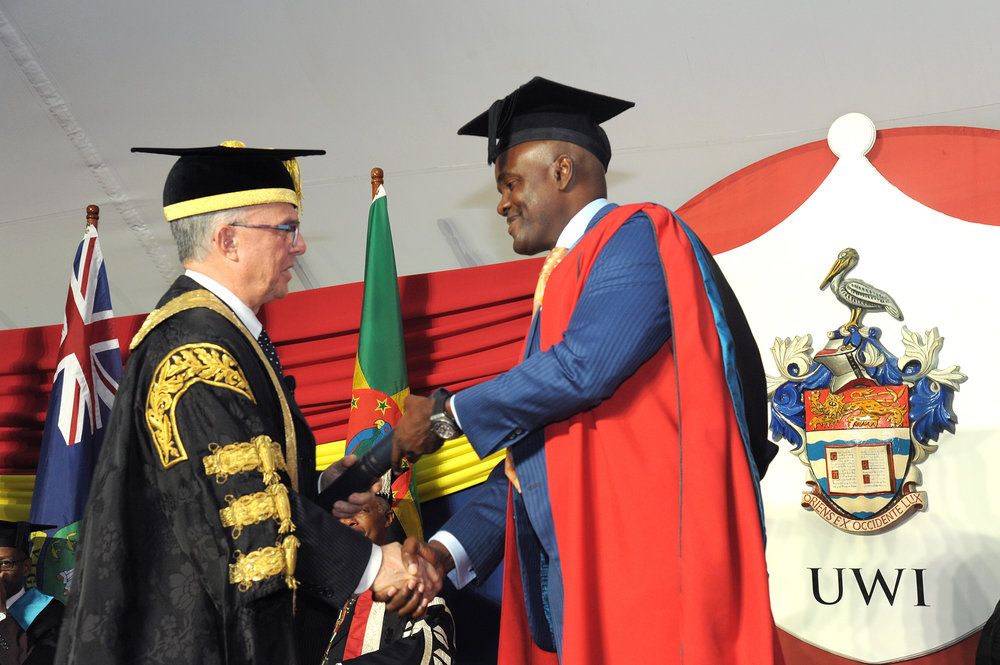 Wes Hall receives his honourary doctorate from UWI chancellor Richard Bermudez