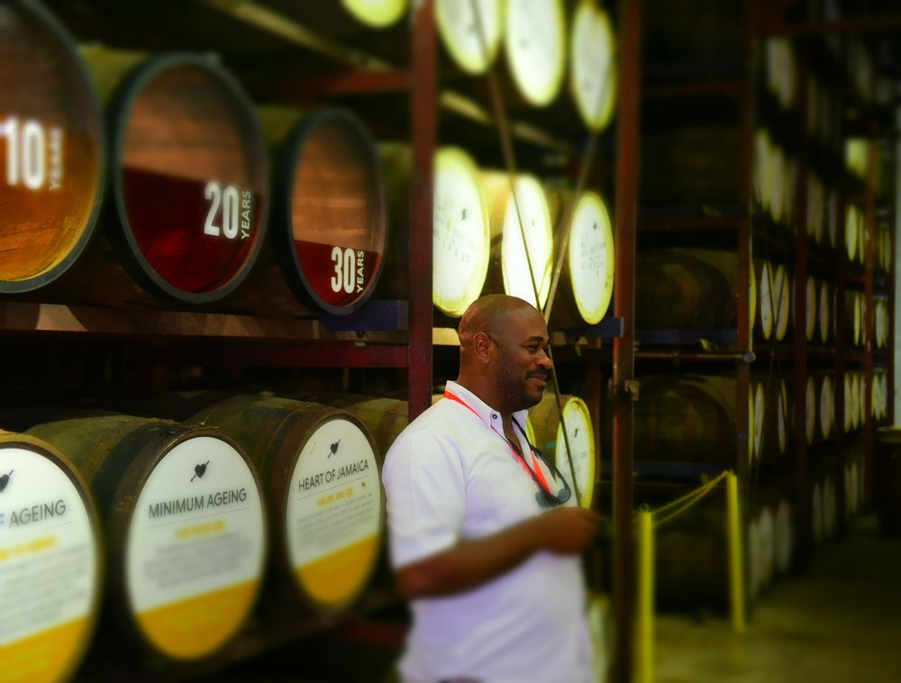 Tour guide Kayon Wright stands next to oak barrels