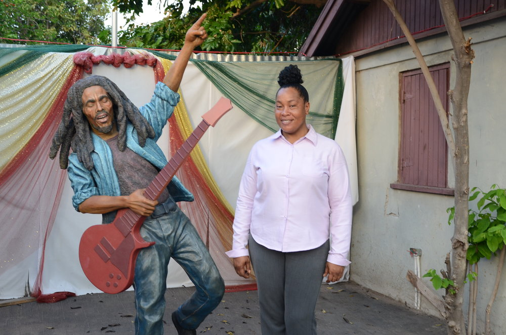 Trenchtown Culture Yard Museum chief tour guide Donnette Dowe stands next to a donated sculpture of Bob Marley