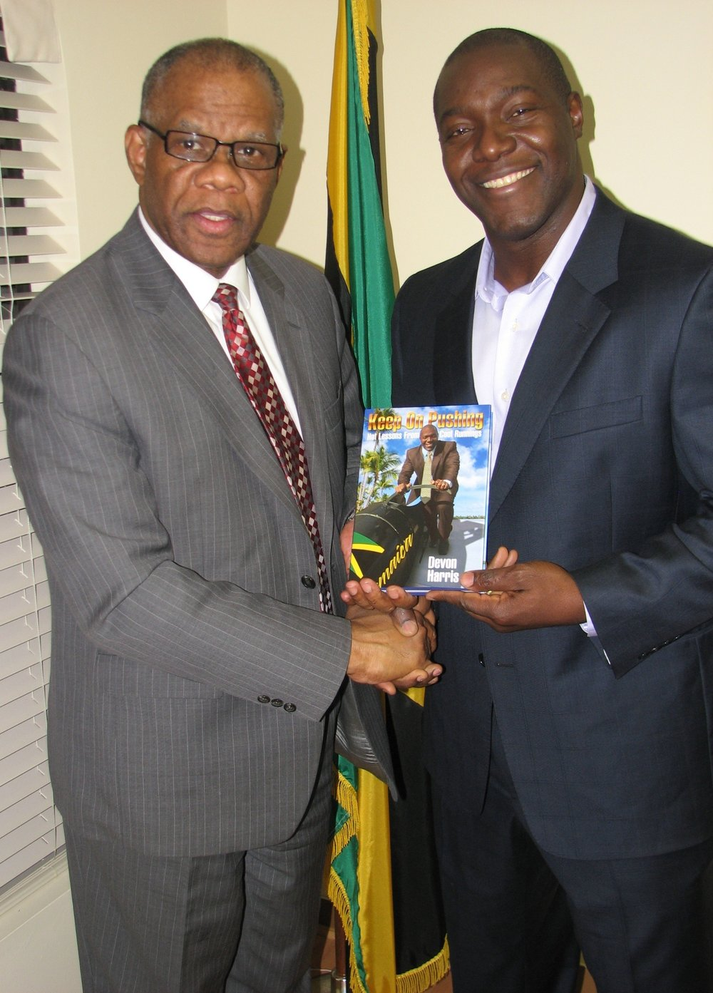 Devon Harris presents a copy of 'Keep on Pushing: Hot Lessons from Cool Runnings' to former Jamaica consul general to Toronto George Ramocan