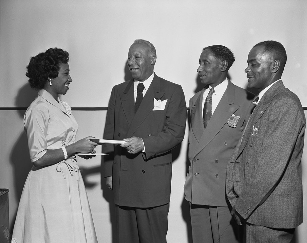 President of the International Brotherhood of Sleeping Car Porters Philip Randolph presents a purse to Violent King-Henry in the presence second vice-president Bennie Smith and Roy Williams (r)