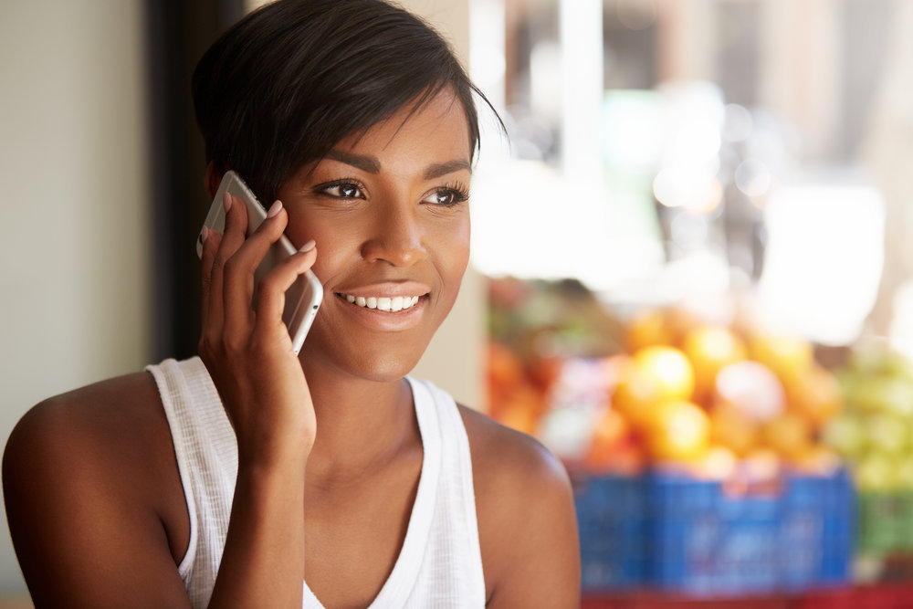 Technology and communication concept. Headshot of fashionable dark-skinned brunette woman with short haircut, laughing while talking to her boyfriend on smart phone, spending free time outdoors