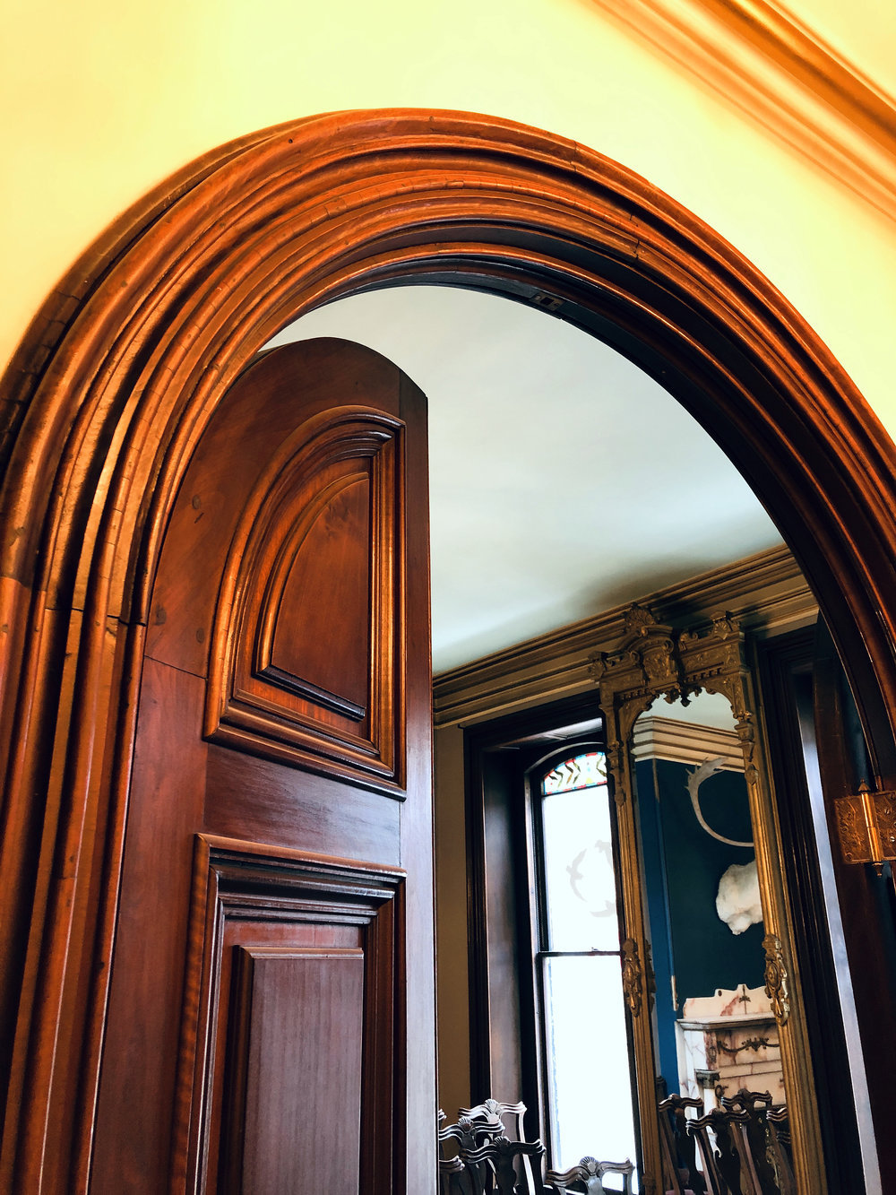 A wooden arch covers a set of 10' tall half moon doors leading to the coffee bar