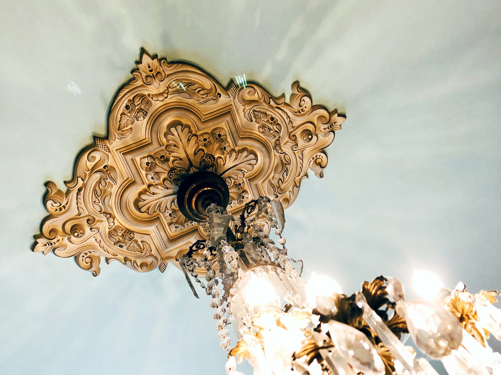The ceiling medallion over the chandelier at the coffee bar includes small details of birds and flowers