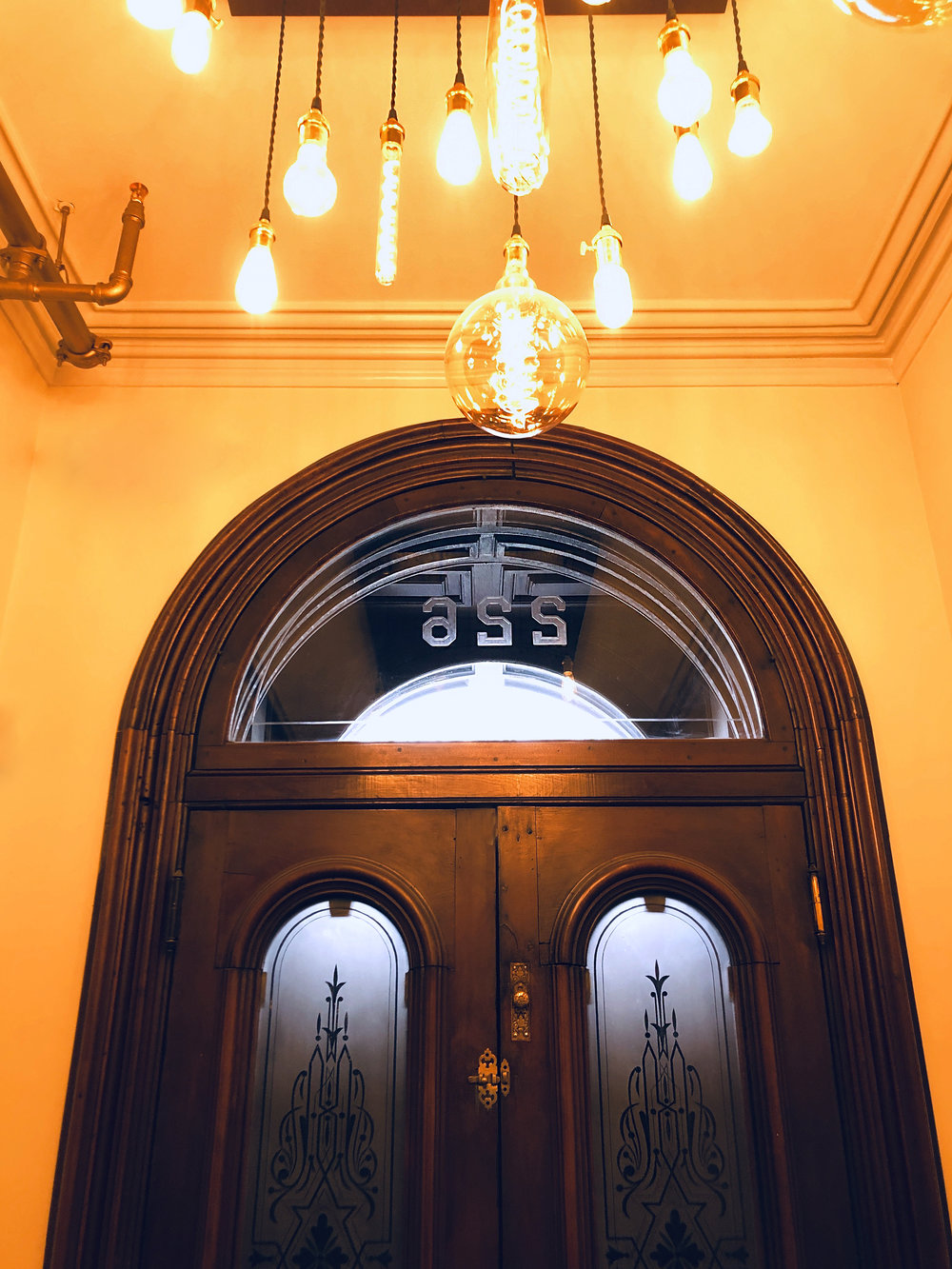 A contemporary chandelier hangs above the original pair of front doors
