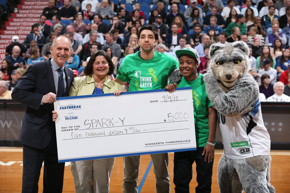 Mary Helen Franze and Zach Robinson receive grant at half court during a Timberwolves game in 2014.