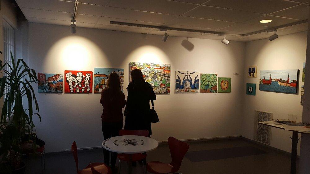 Några besökare står och beundrar min medutställare och konstnärsväns, Orsi Milds tavlor.