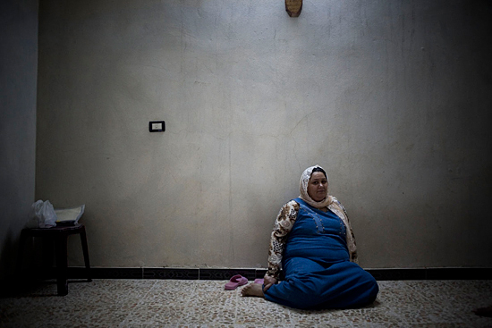 Iraqi refugee, pregnant after 15 years of marriage, sits in her bare apartment. Damascus, Syria, 2008