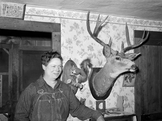 Mildred Anthony, standing by mounted animals which she killed.