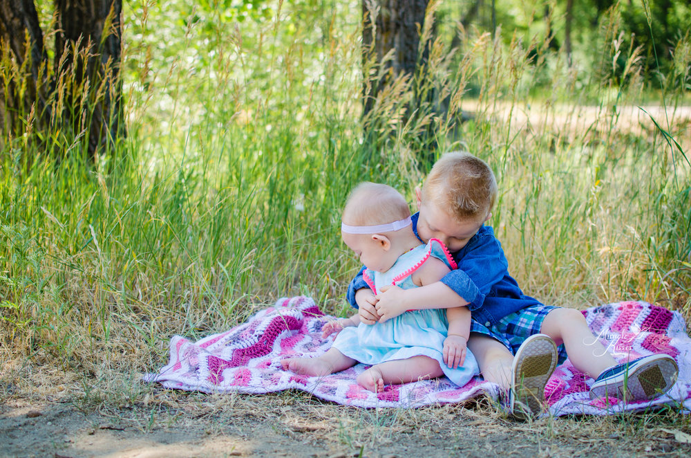Siblings hugging in the grass, love, child photography