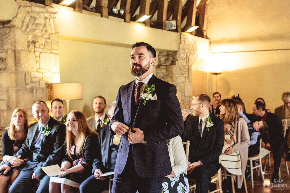 Boho Groom awaiting Bride in Gieves & Hawkes Suit at Blackfrairs Priory in Gloucester