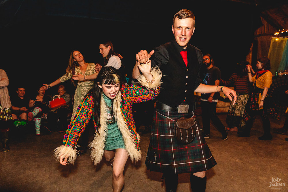 Two guests dancing wildly, girl wearing alternative muilti-coloured coat and groomsman wearing kilt at fun DIY festival wedding in a Barn | Shropshire wedding photographer