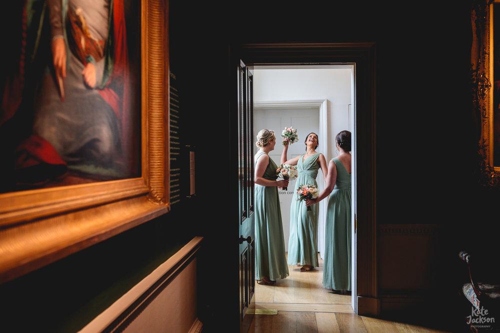 Fun bridesmaids striking a pose through a doorway at Compton Verney Wedding