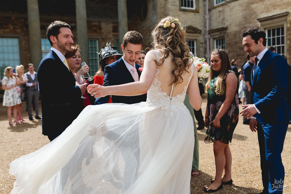 Brides dress blowing in the wind and guests exclaiming at Compton Verney alternative wedding in Warwickshire