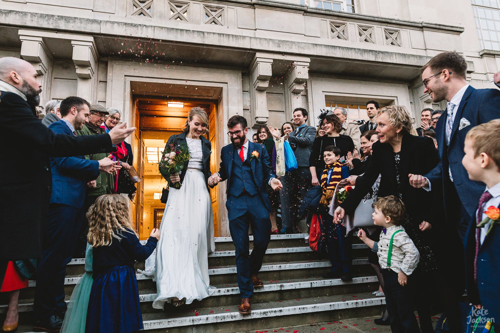 Alternative bride and groom walking down steps during fun confetti photo outside of Hackney Town Hall