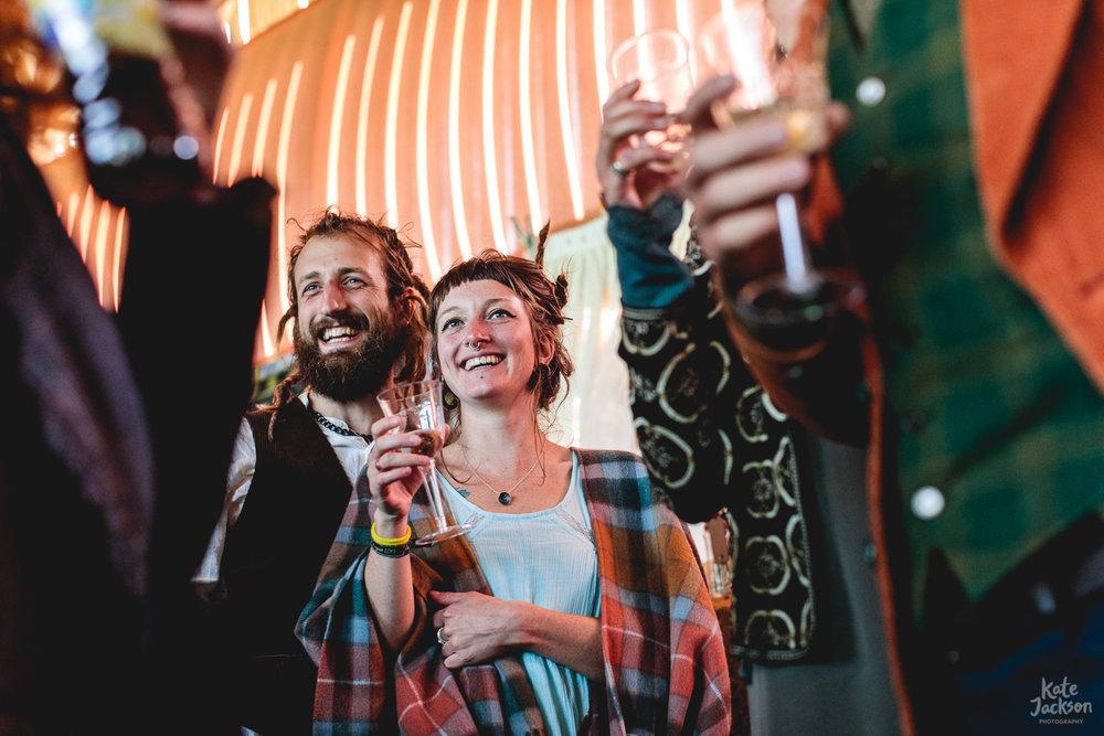 Wedding guests standing and raising a glass in barn at fun diy festival wedding | Shropshire Wedding Photographer