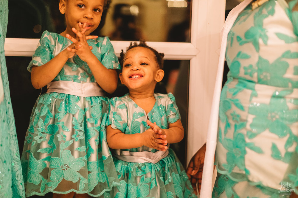 Natural photo of little bridesmaids smiling at those around them in colourful turquoise dresses at Fazeley Studios wedding in Birmingham