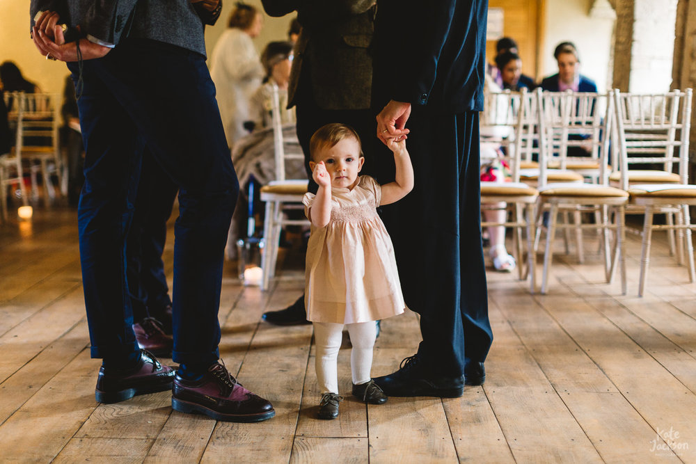 Toddler stood in the ceremony room at relaxed spring wedding at Blackfriars Priory in Gloucestershire | Alternative Wedding Photographer