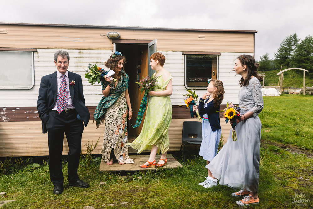 Bridal party stood outside of caravan in a field pre ceremony at outdoor DIY Festival Wedding | Shropshire Photographer