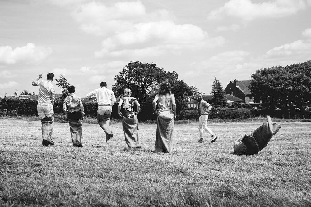Guests sack racing during wedding games at fun diy festival wedding in Sheffield