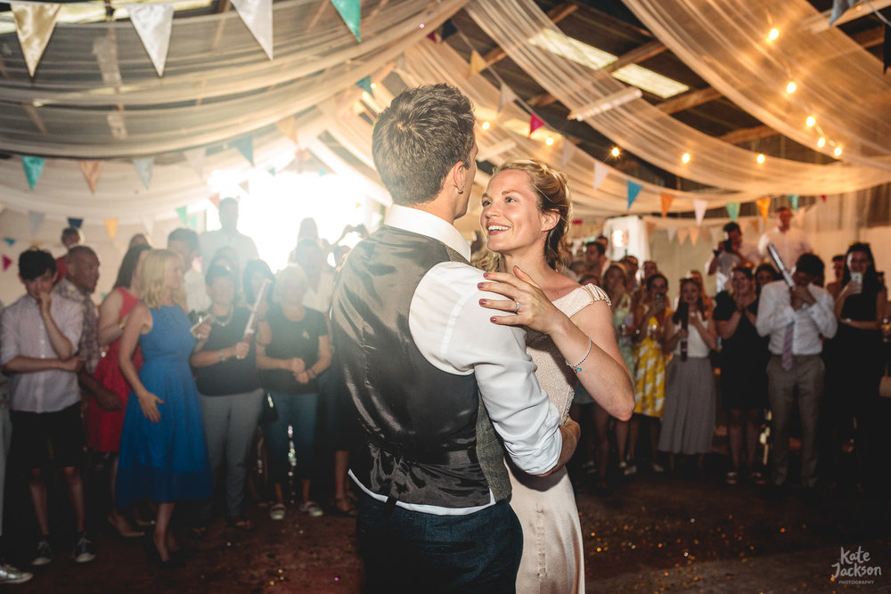 Bride and groom having first dance to Bloc Party in barn full of festival bunting at fun wedding in Sheffield | Alternative wedding photographer