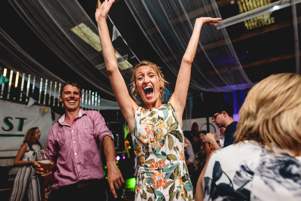 Fun photo of lady dancing with her arms in the air looking at the camera singing at alternative festival wedding in a barn in sheffield