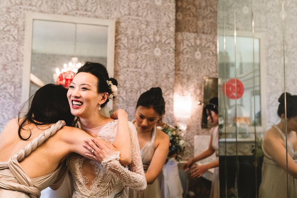 Bride smiling joyfully as she embraces bridesmaid in room at Babbington House in Bath