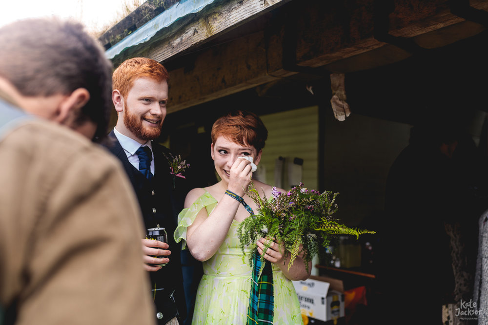 Bridesmaid in alternative light green dress with a pixie hair cut dabs at eyes with a tissue after emotional humanist wedding ceremony in Shropshire