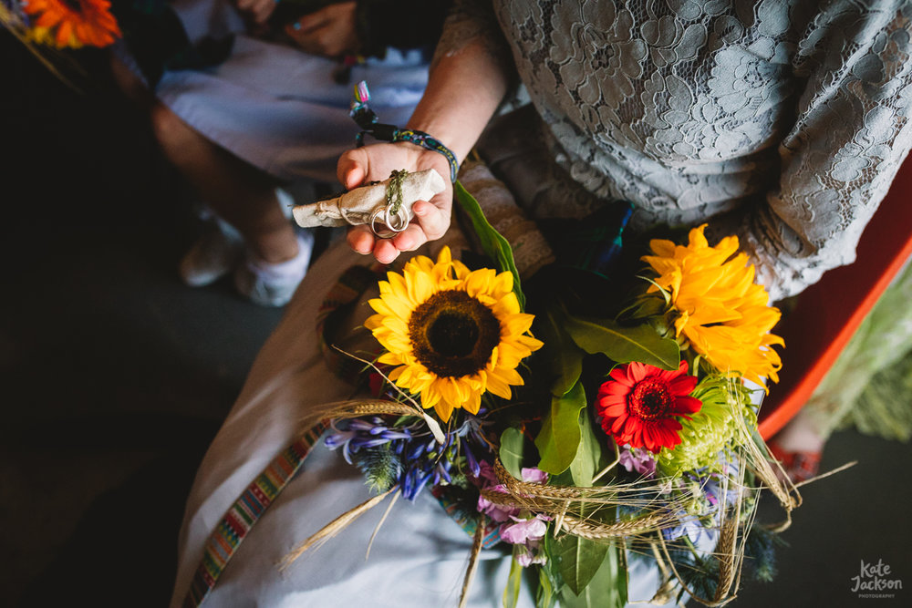 Wedding ring blessing at humanist festival wedding, photo of bridesmaids hand with the wedding rings and her diy bouquet of sunflowers and other summer flowers