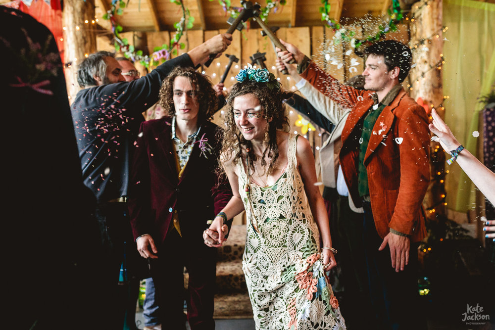 Alternative indoor confetti photo of bride and groom exit under hammer arch with lavender thrown at them
