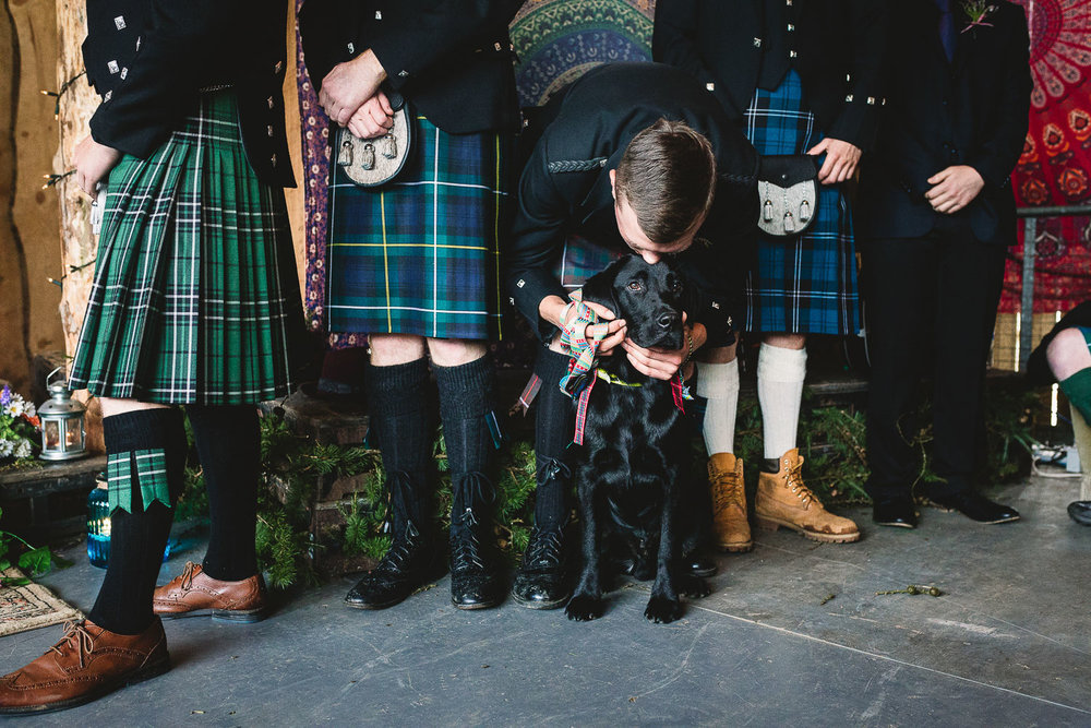 Groomsman in kilt bending down to kiss labrador during fun humanist wedding ceremony in Warwickshire