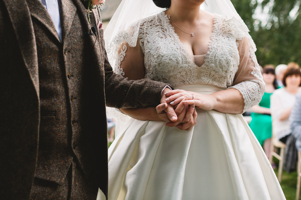 Bride and groom hold hands in natural candid moment during Hyde Barn Wedding ceremony