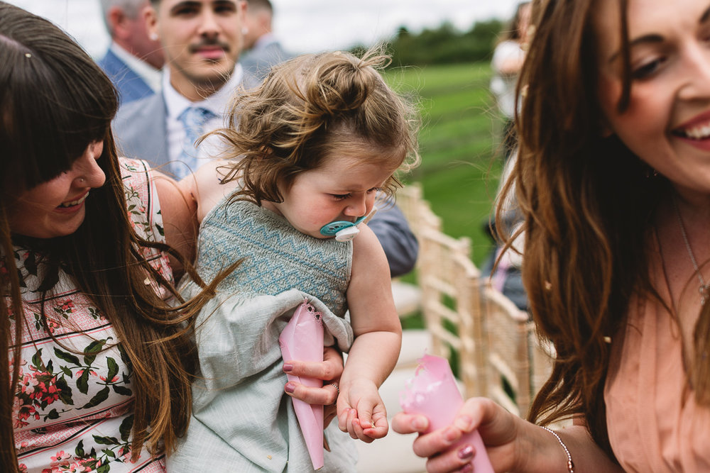 Child at wedding holds confetti | Candid Wedding Photos at Hyde Barn