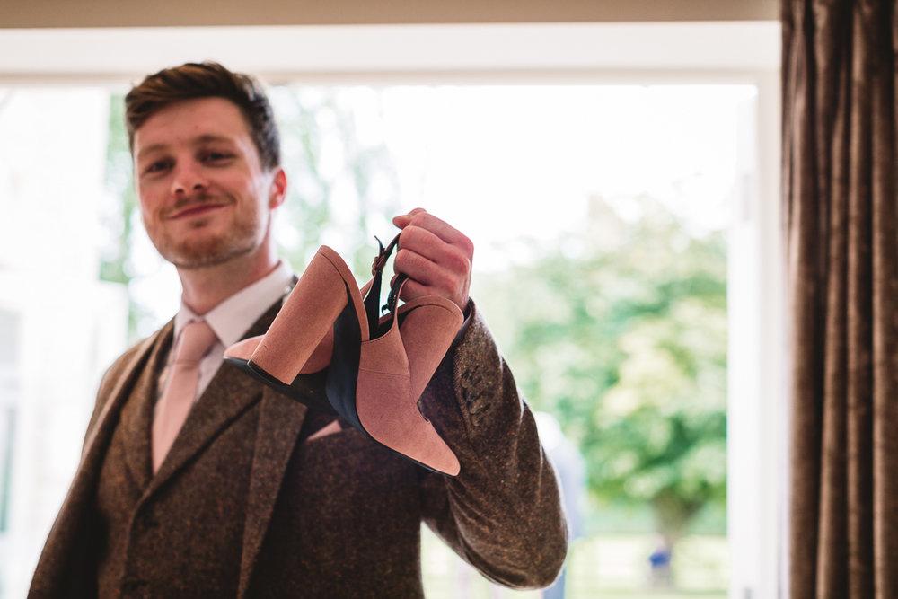 Groomsman holds bridesmaid shoes at fun Hyde Barn Wedding