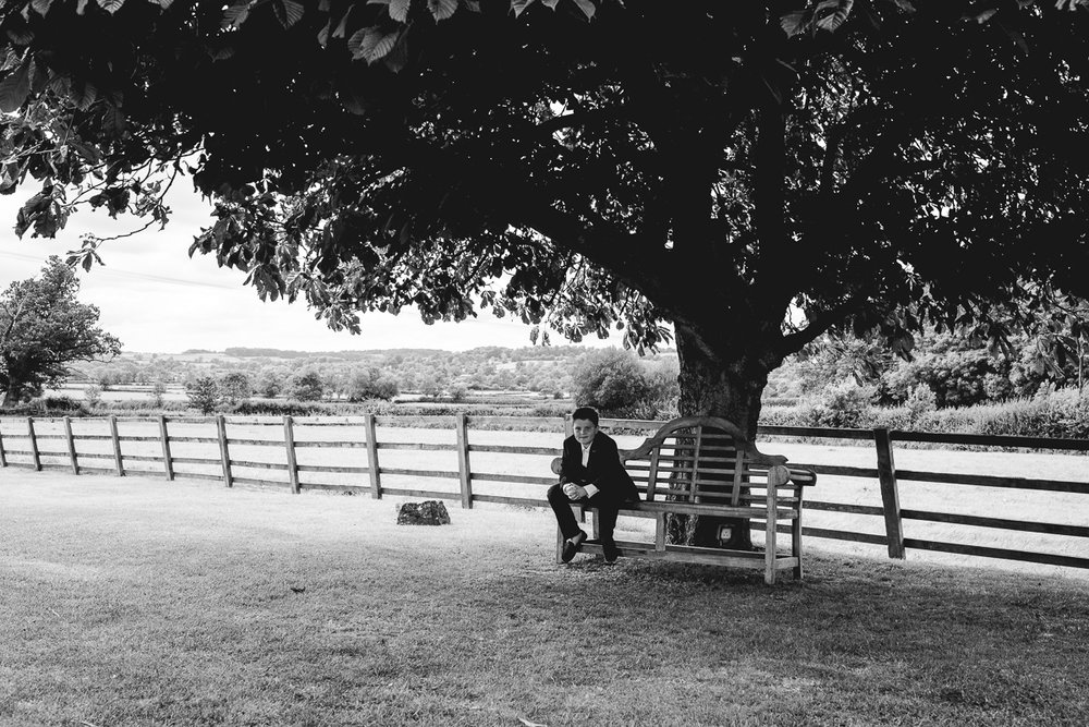 Man relaxes on bench at relaxed Hyde Barn Wedding