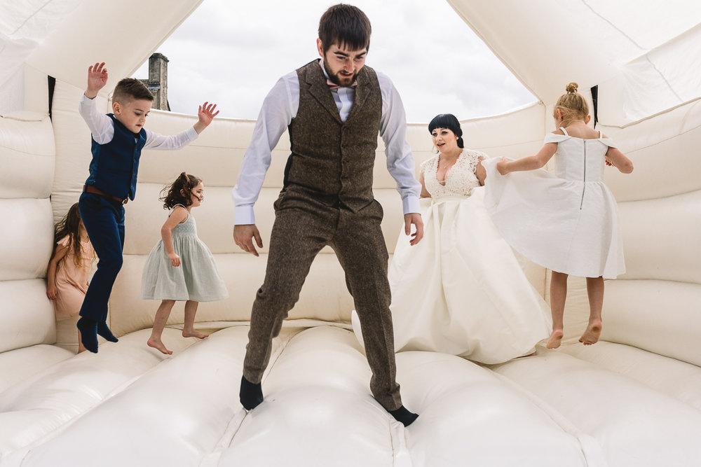 Groom having fun in vintage style suit on white wedding bouncy castle