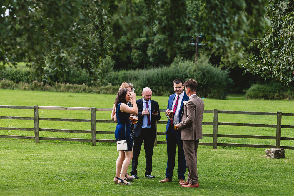 Guests chat outdoors at relaxed hyde barn weddings