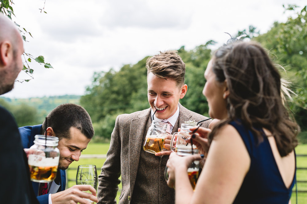 Fun photo of guests drinking summer Pimms at Hyde Barn Weddings