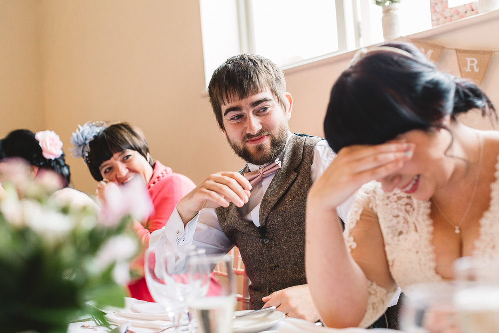 Groom laughing at funny wedding speech
