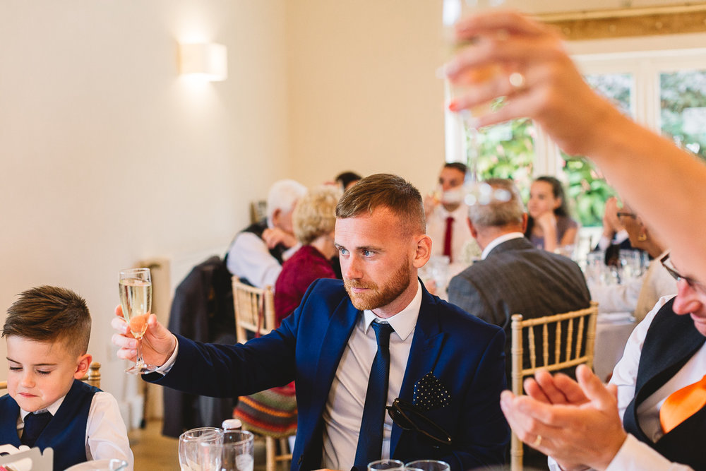 Cheers with prosecco at fun hyde barn wedding