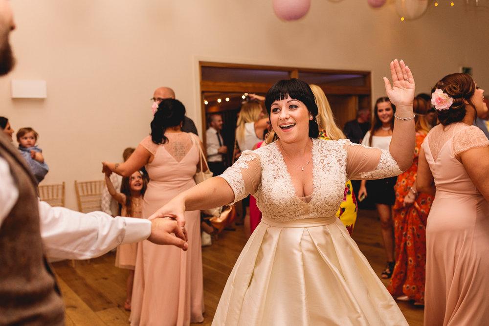 Bride in a berketex bridal dress has fun dancing in cotswolds