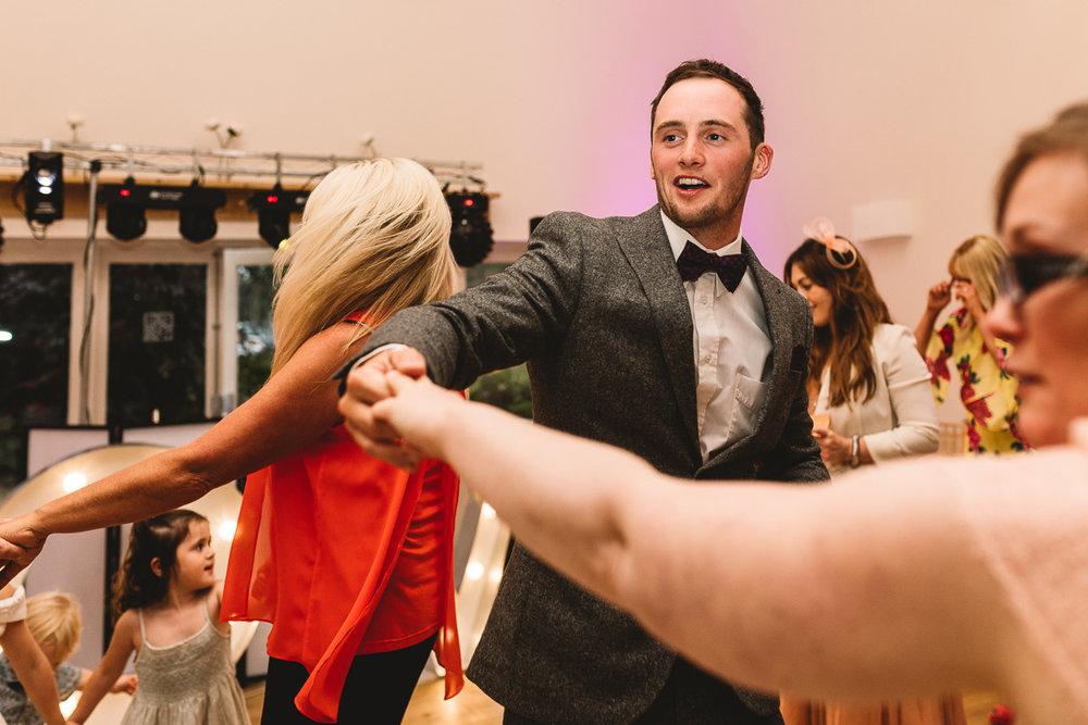 Man in fun bow tie dances at hyde barn wedding
